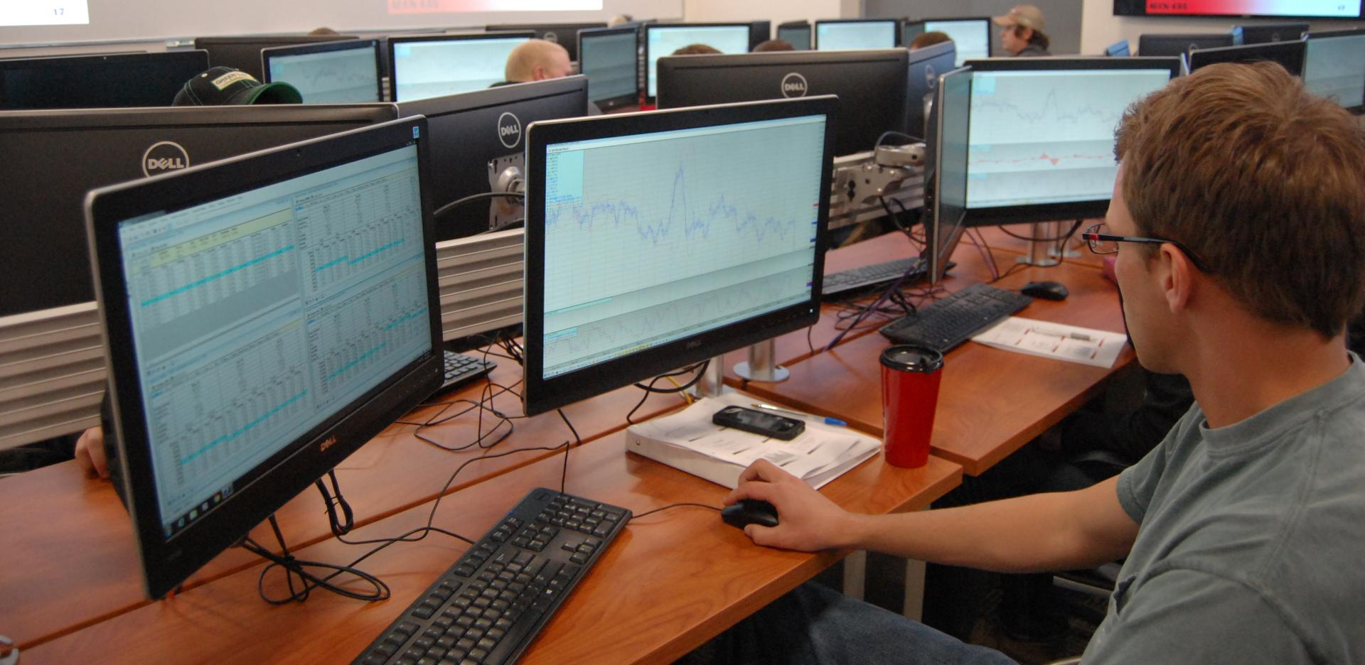Student checking markets in the commodity trading room